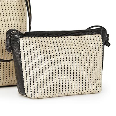 Kleine Tasche, bestehend aus cremefarbenen Lederbändchen, welche auf schwarzen Lederfond genäht sind.